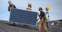 Members of Iron and Earth installign a solar panel on a roof.